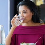 A woman having lunch and drinking a glass of purified water